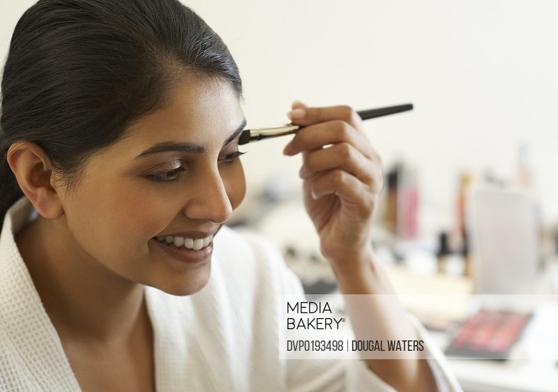 Asian woman applying make up