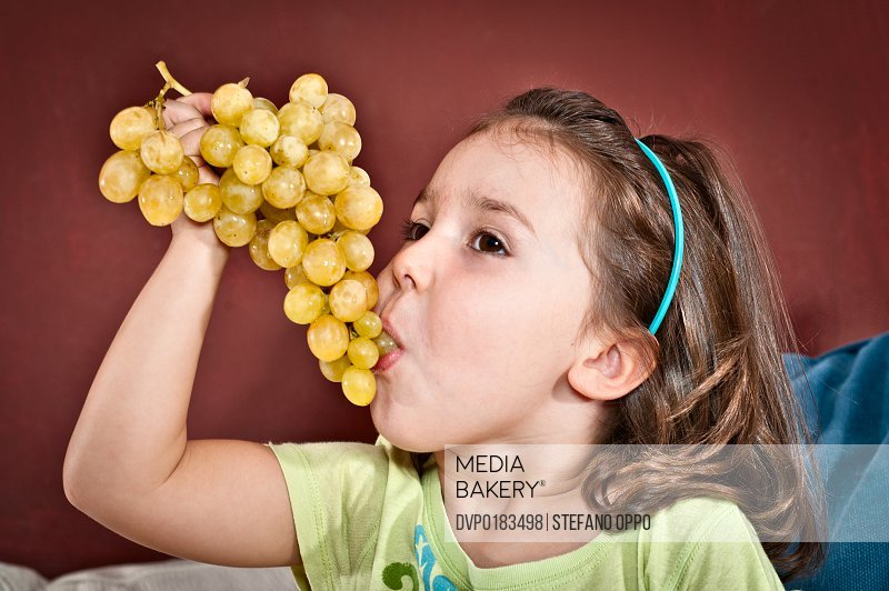 Little girl with bunch of grape