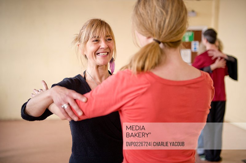 Yoga instructor and student working on tango embrace