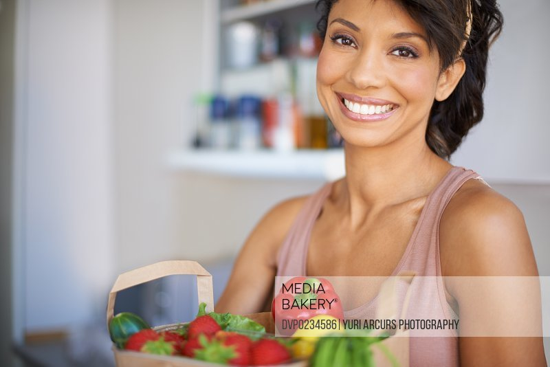 A beautiful young woman holding a shopping bag full of fresh produce