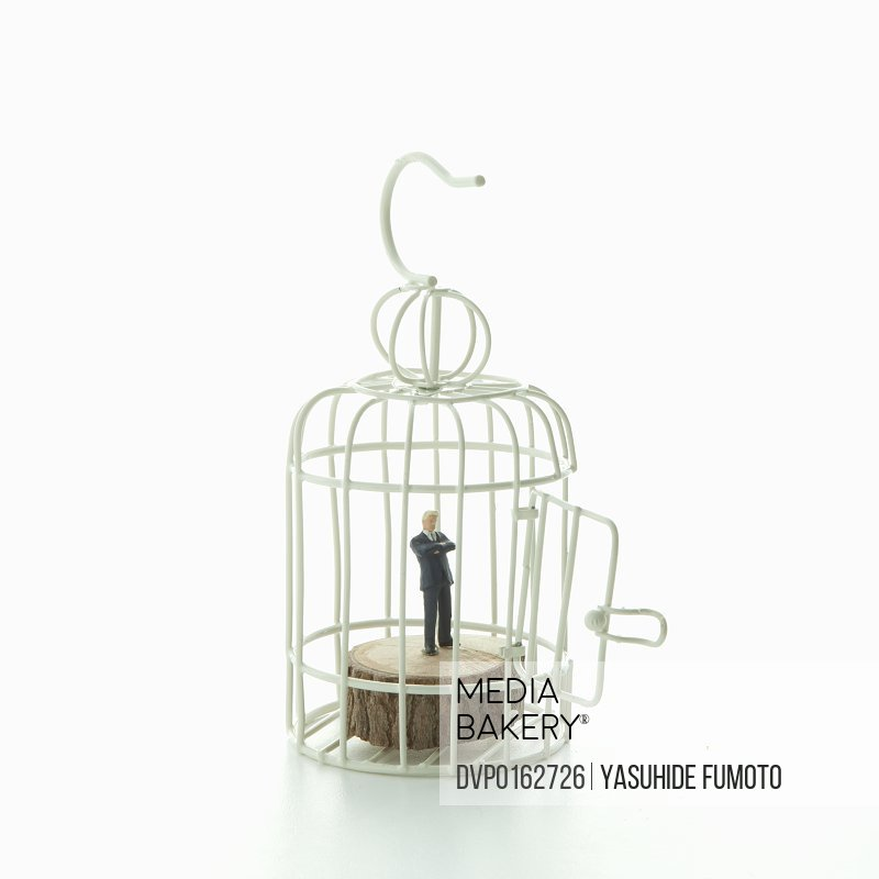 Miniature businessman figure in the cage.