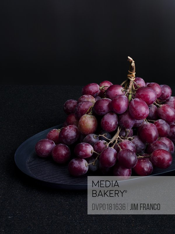 Red grapes on dark table