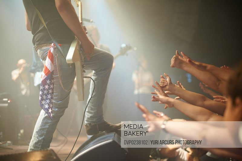 Shot of a crowd of music fans reaching up at a guitarist on stage