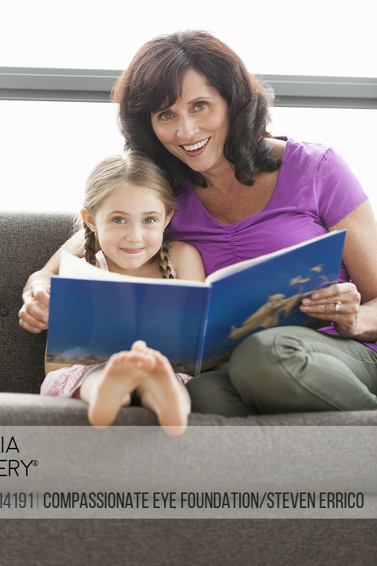 Grandmother and granddaughter on sofa reading book