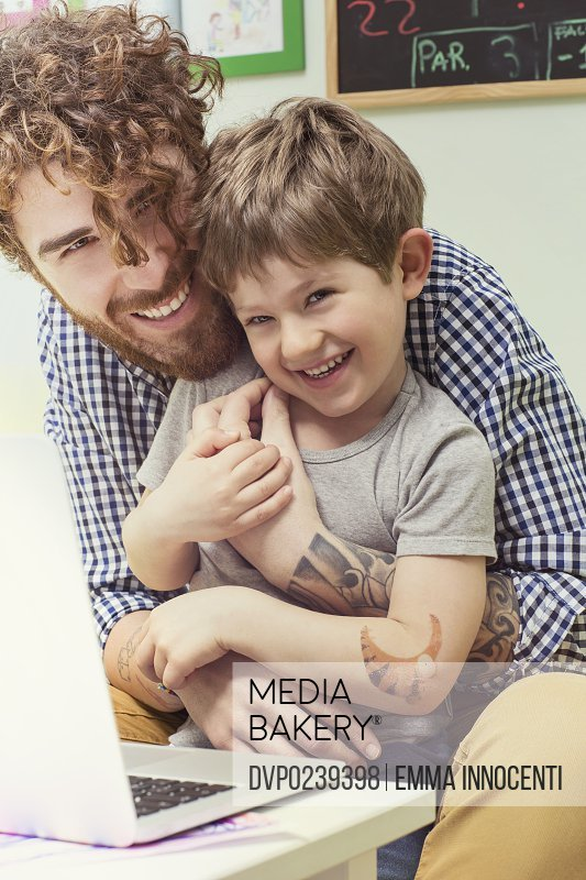 indoors, dad, child, technology, wireless technology, sitting, sofa, happiness, toothy smile, holding, playing, arm around, looking at camera, embracing, joking, laughing, toothy smile, laptop computer, tattoos, bearded, casual clothes, checked shirt
