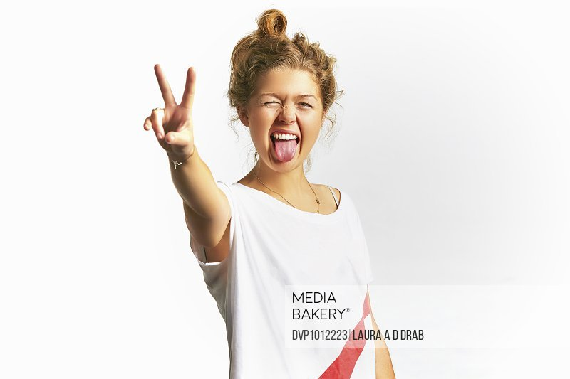 Young woman sticking tongue out making peace sign