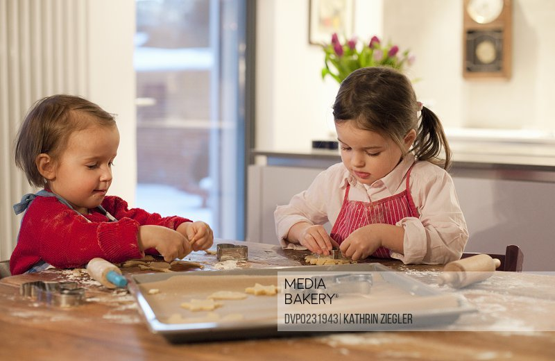 two little girls making cookies