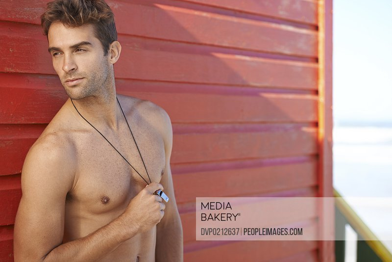 Shot of an attractive male lifeguard standing confidently and holding his whistle