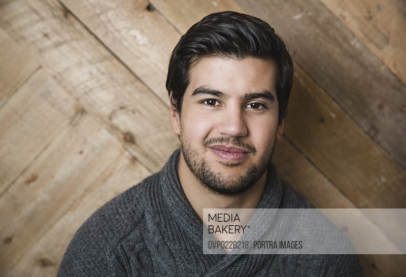 Portrait of confident young man against wooden wall