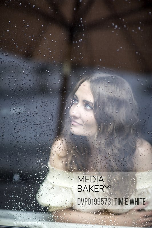 Woman inside looking at the rain on a window