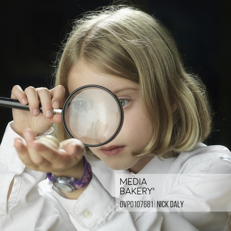 Schoolgirl (8-10) looking at shell through magnifying glass