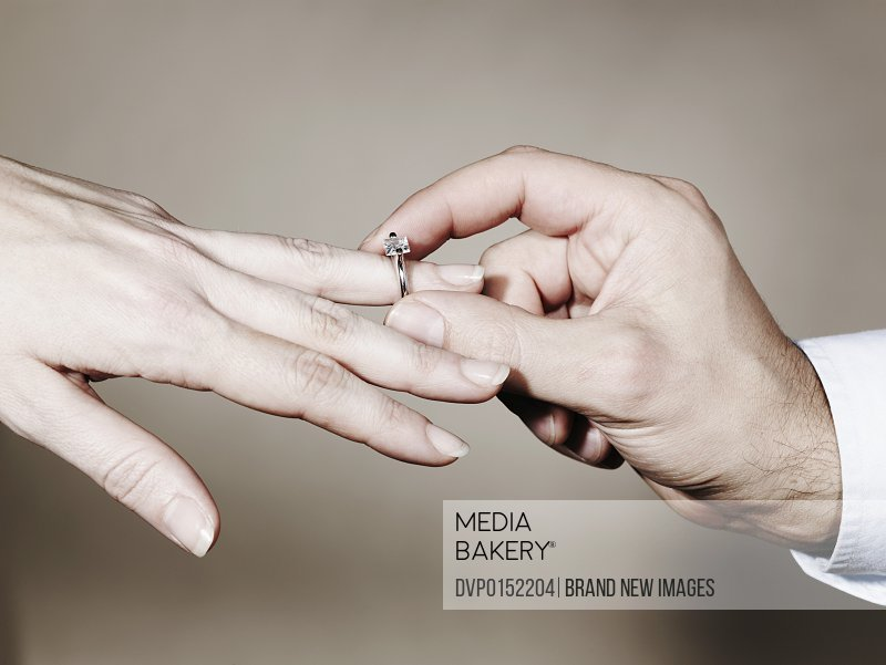 Hands of couple with engagement ring