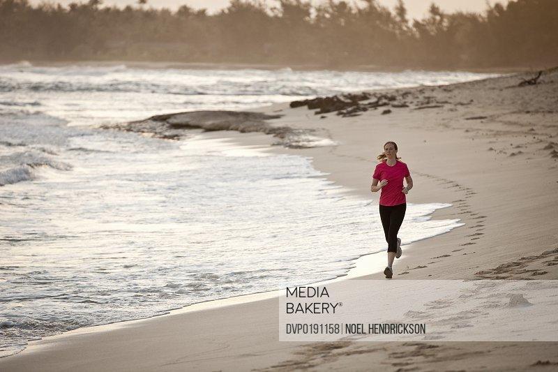 A woman runs on the beach at sunrise