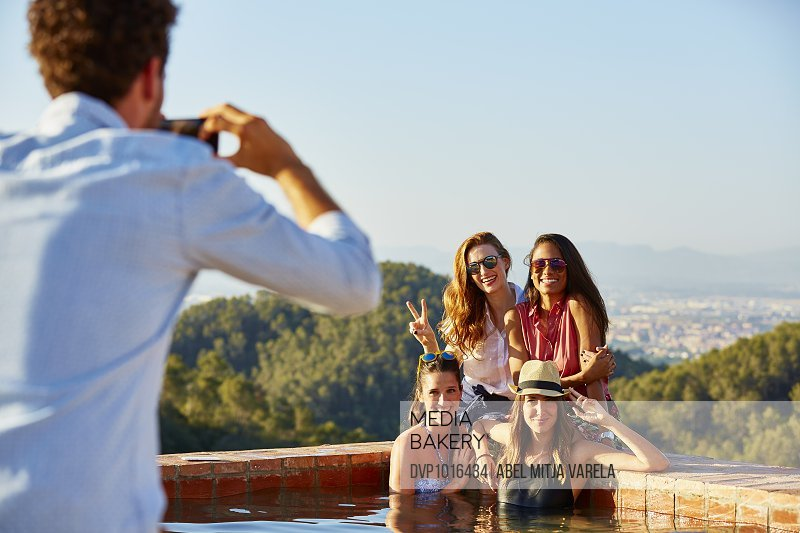 Man photographing female friends at pool's edge