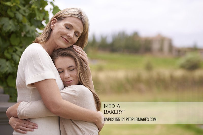 A mother embracing her daughter in an outdoor setting