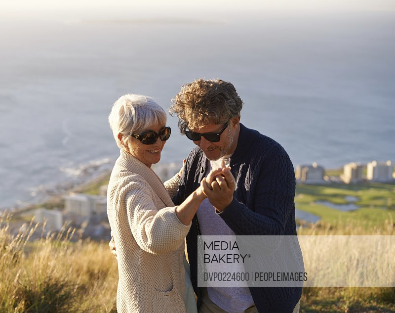 Cropped view of a senior couple dancing on a hillside together