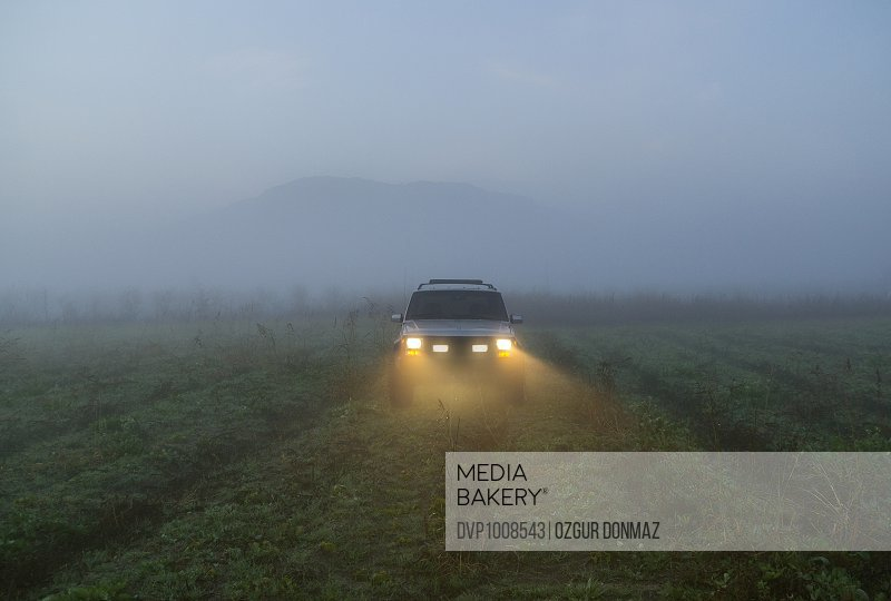 Off road vehicle driving in a foggy morning