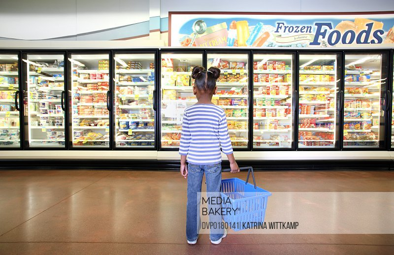 A four-year-old girl stands in the frozen food section of the grocery store