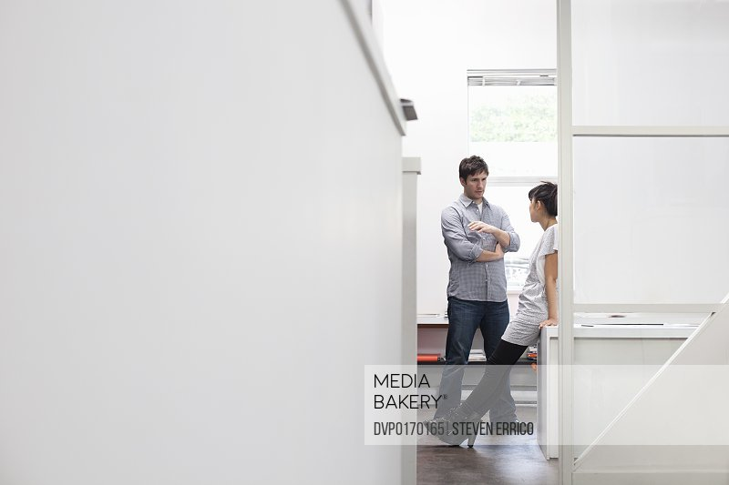 Young casually dressed Caucasian man and Asian woman discussing ideas in office of a modern creative agency