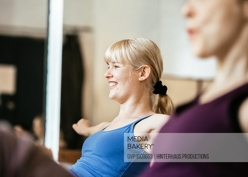 Woman sitting on floor and training abdominals in workout class