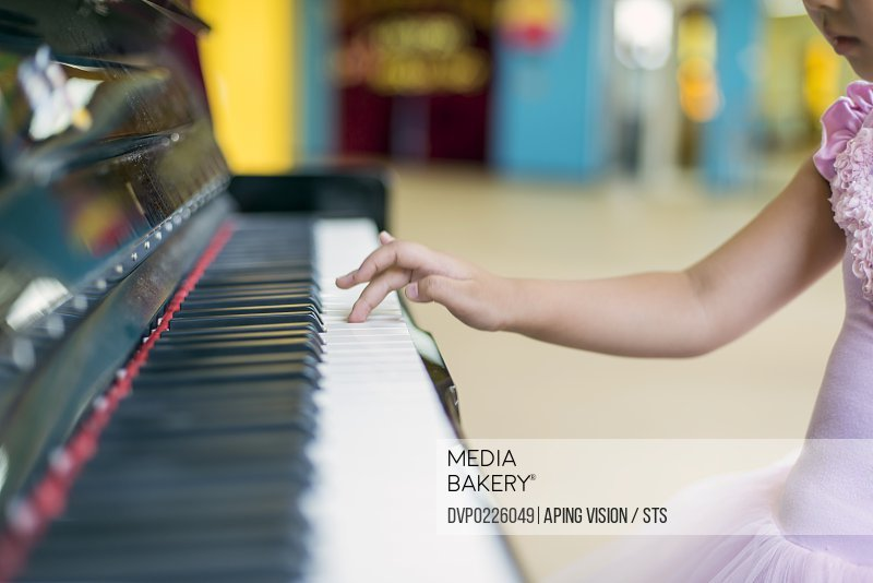 little girl playing piano in kindergarten