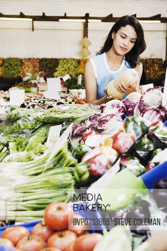 Woman selecting vegetables at market stall