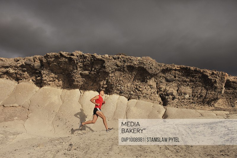 Man in red t-shirt running on rock, stormy sky