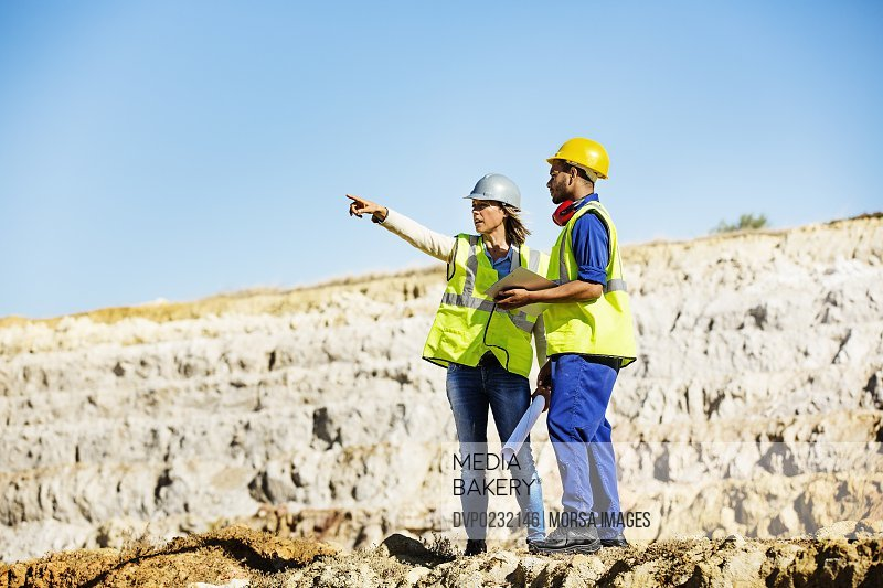 Architect explaining plan to quarry worker at site