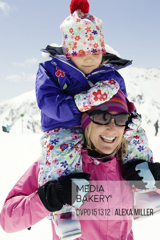 Winter portrait of mom with daughter on shoulders