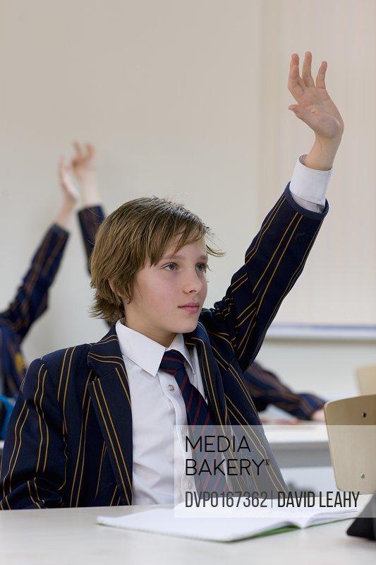 Boy in school uniform with his arm raised in classroom