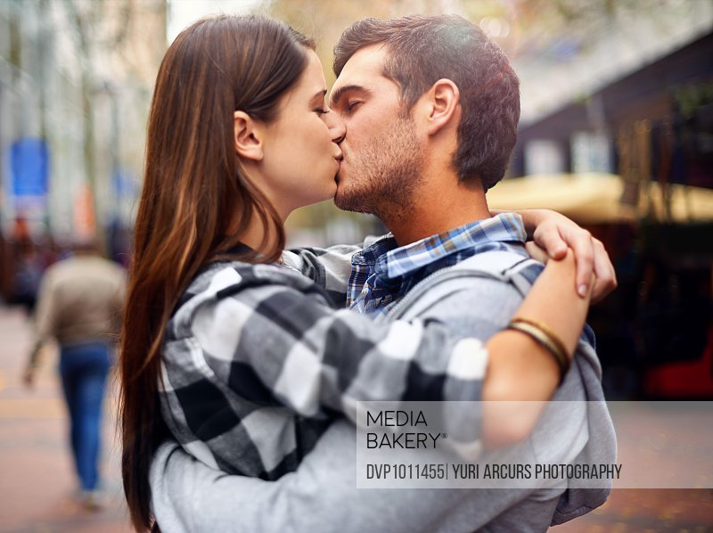 Shot of a young couple kissing in a downtown street