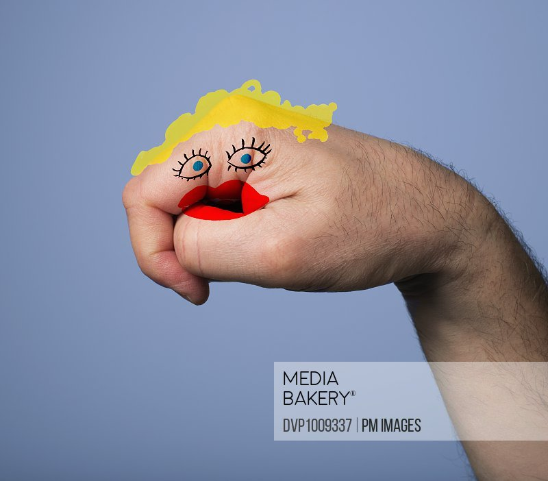 Man's hand with a woman's face drawn on it, blonde hair, blue eyes and red lips