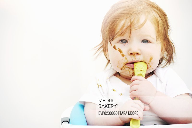 Toddler looking messy face covered in food