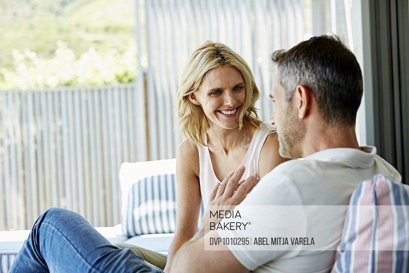 Smiling woman listening to man at home