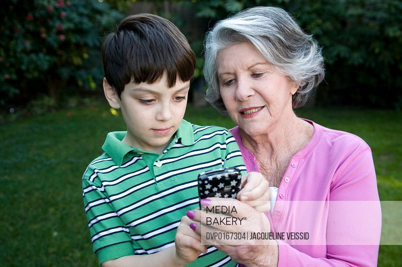 Boy showing grandmother how mobile device works