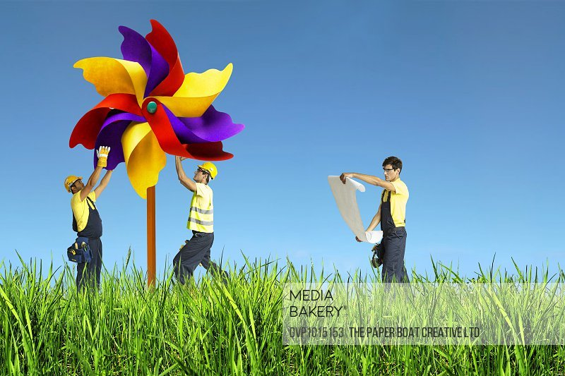 group of tiny men fixing a giant pinwheel in grass