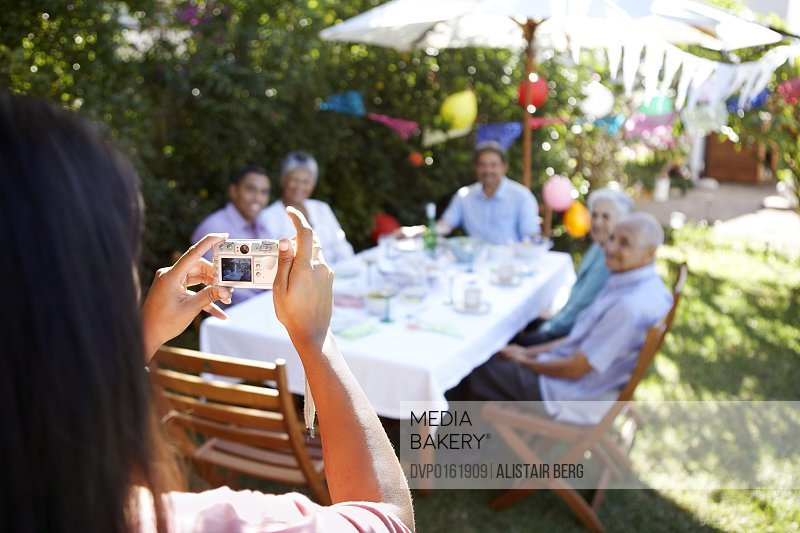 Woman in forground using a gdigital camera to take a picture of a family group celebrating a birthday together outdoors.
