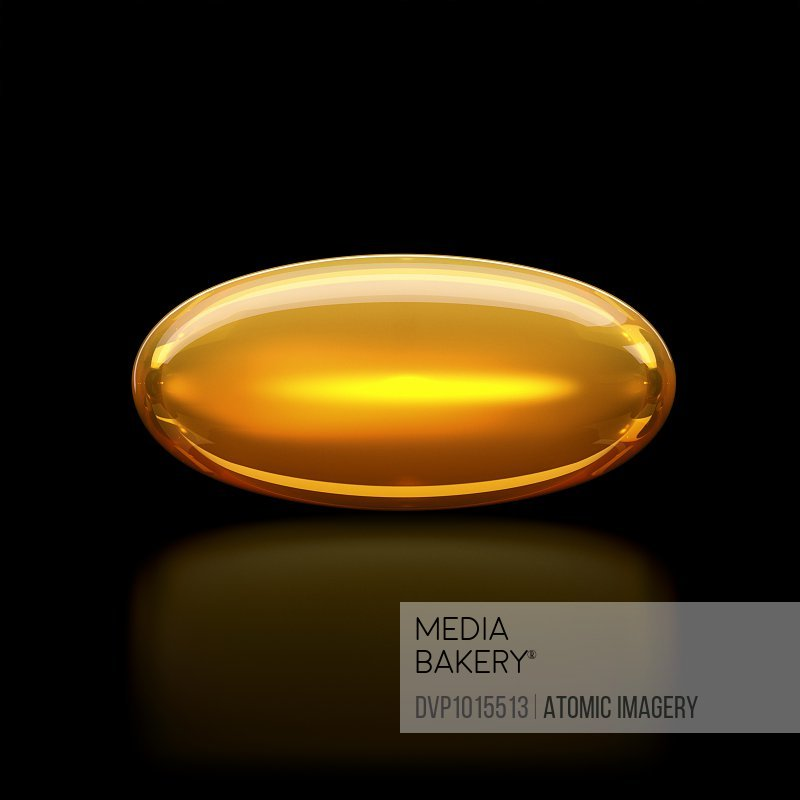 Oil / medication pill capsule on black surface