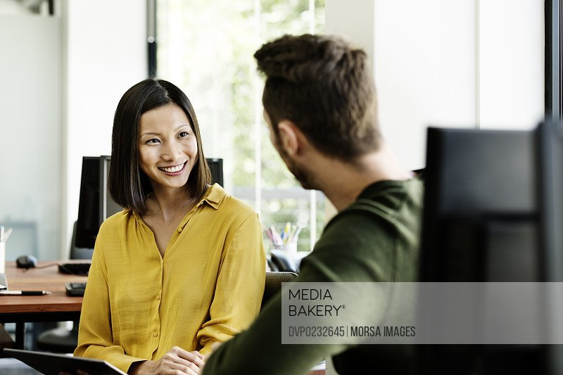 Happy businesswoman discussing with male colleague in office
