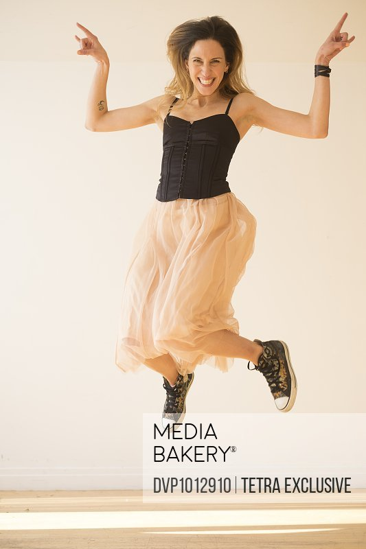 Portrait of young woman in black top jumping