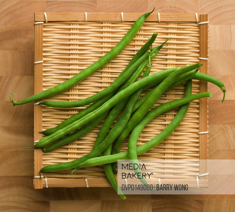 Bunch of fresh green beans on a bamboo tray and wooden cutting board.