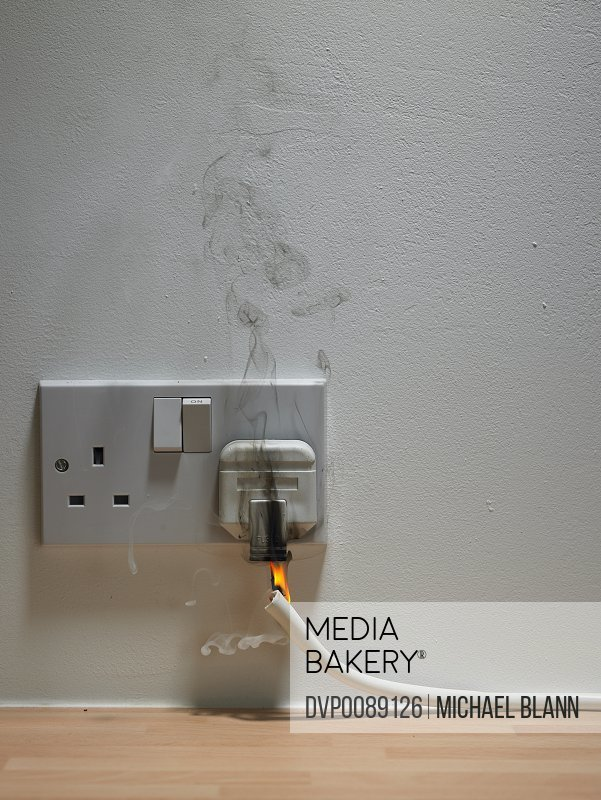 Electric plug in wall outlet with smoke and flame