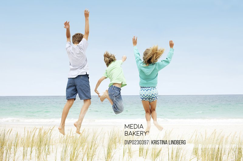 Three kids jumping off a sand dune facing the sea