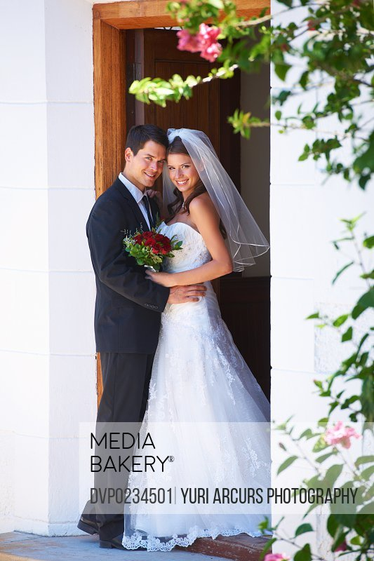 Full length portrait of young newlyweds standing in a church doorway
