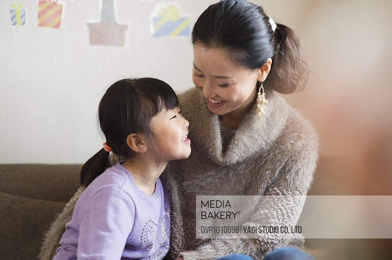 Mother and daughter in room,smiling