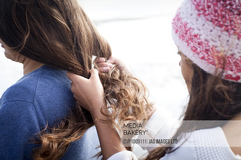 Middle age woman and her teenage daughter - her daughter is Plaiting her hair outside in Bournemouth England in the summer