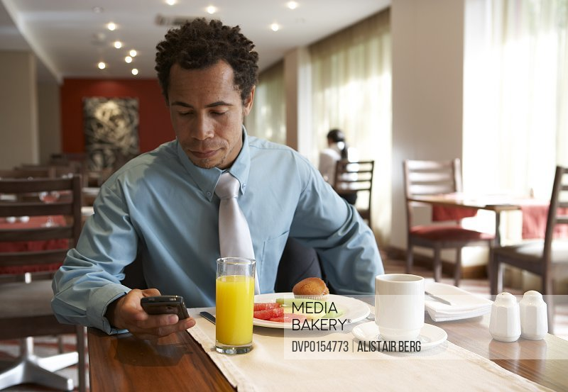 Businessman using a Blackberry style mobile communication device in hotel breakfast room.