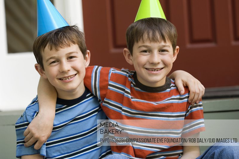twin boys in party hats and striped shirts