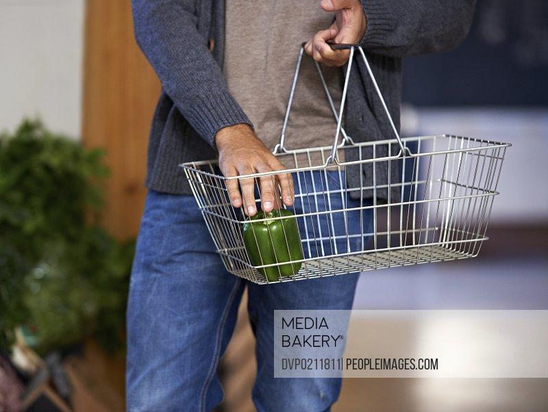Cropped shot of a male shopper placing a pepper into his basket