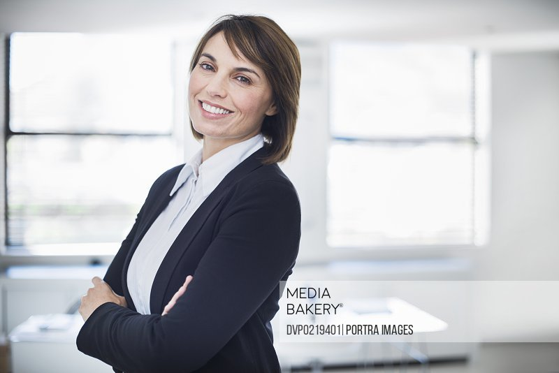 Smiling business woman in her office looking into camera